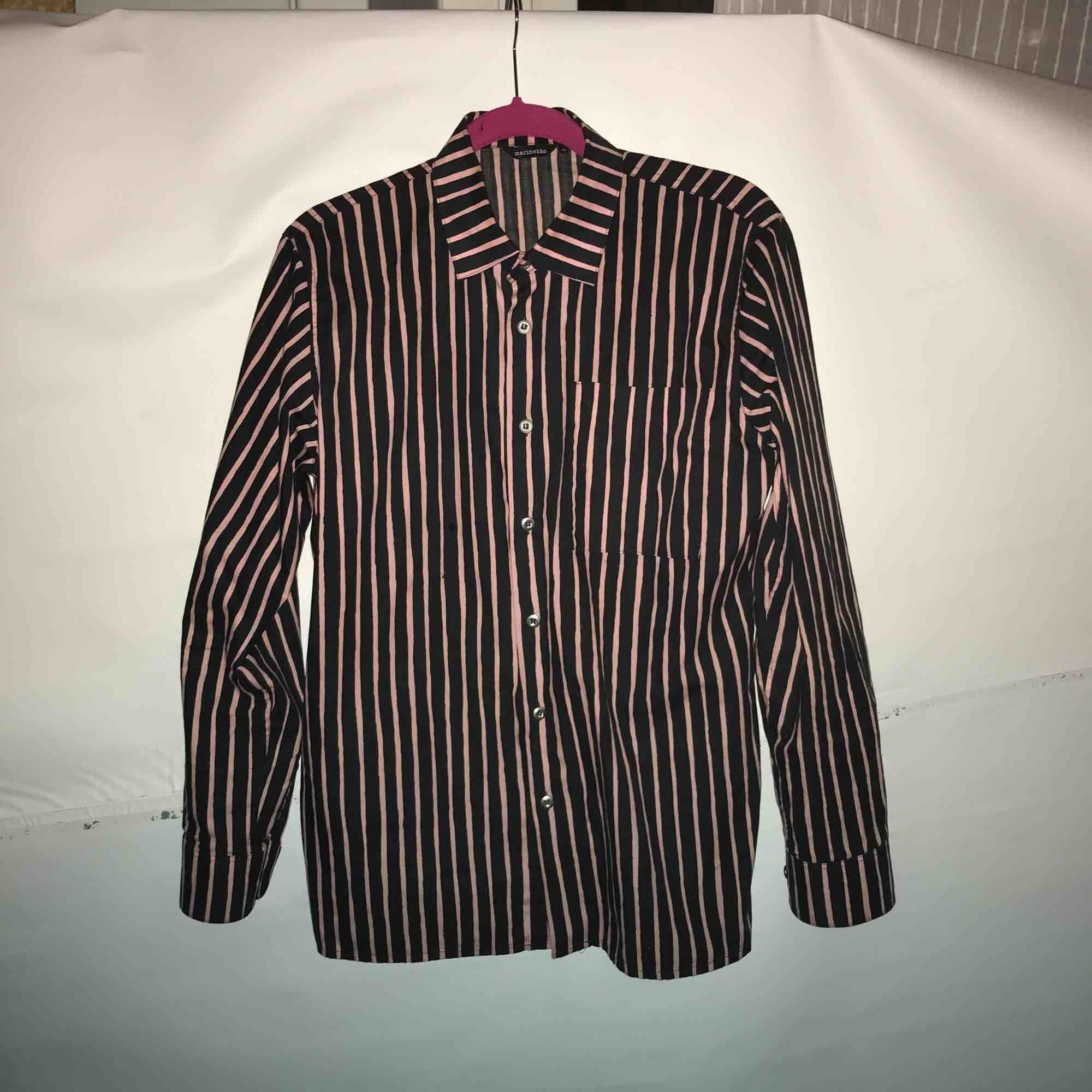 Blå och rosa randig Marrimekko skjorta i storlek XS. Använd fåtal gånger så skjortan är i fint skick! 100% bomull. Boxig i modellen. Kan mötas upp i Stockholm eller fraktas. Köparen står för frakten. . Skjortor.