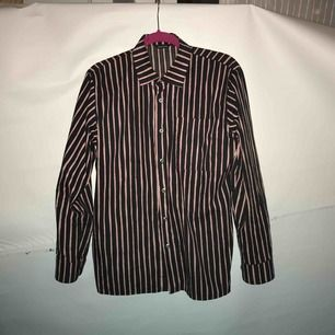 Blå och rosa randig Marrimekko skjorta i storlek XS. Använd fåtal gånger så skjortan är i fint skick! 100% bomull. Boxig i modellen. Kan mötas upp i Stockholm eller fraktas. Köparen står för frakten.