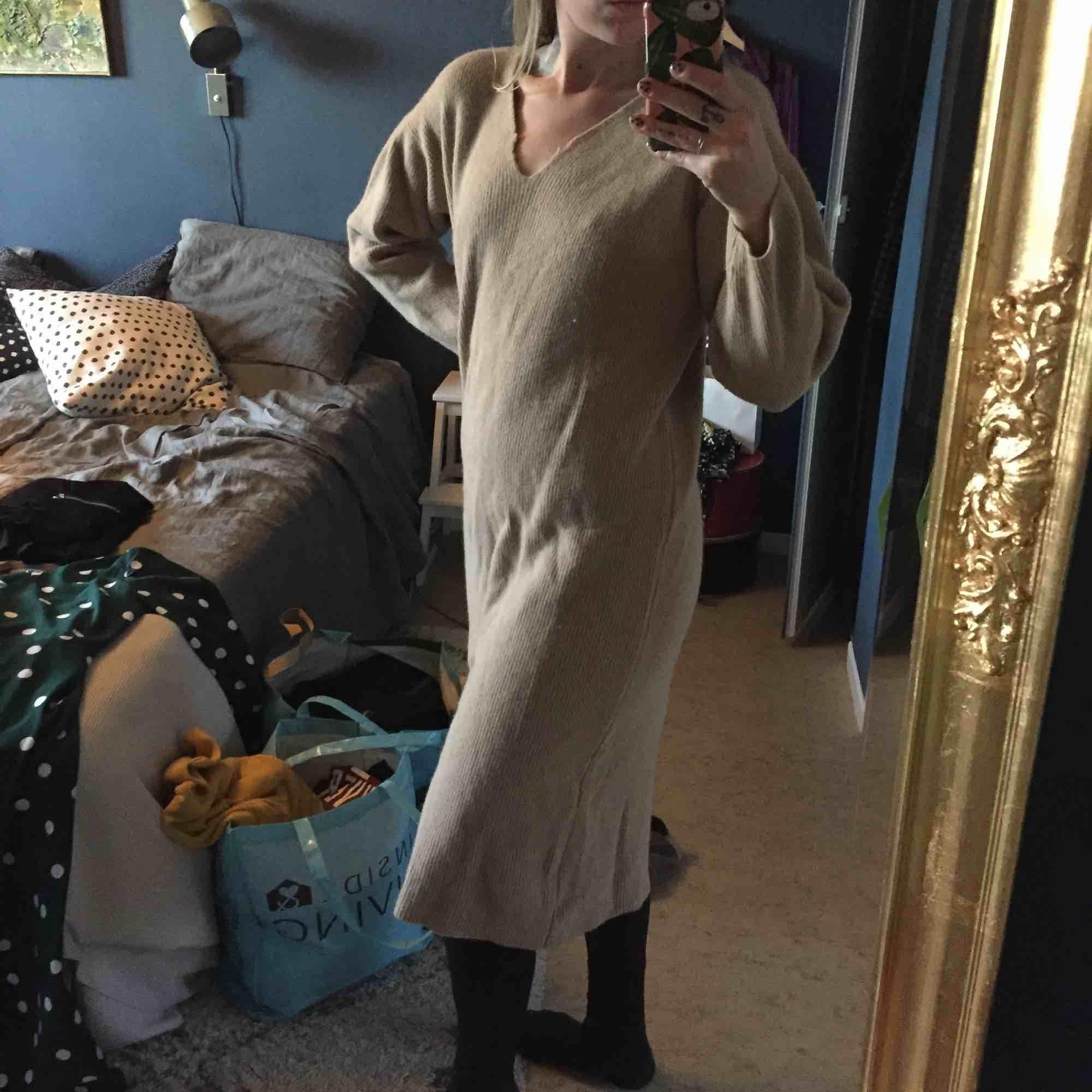Beige långklänning/tröja. Osäker på material, den sticks inte men känns som ull eller liknande. Använt men gott skick. . Stickat.