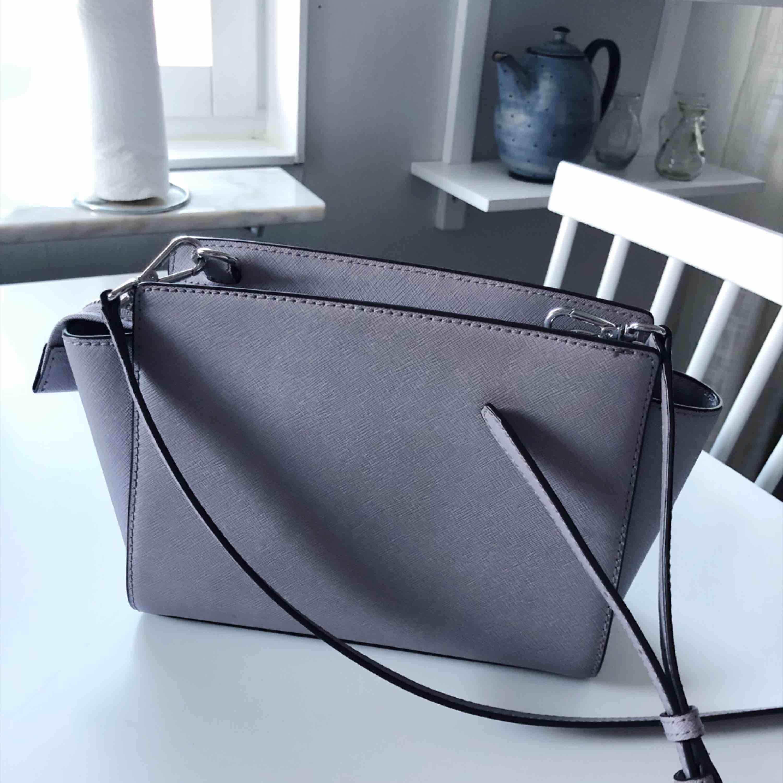 Jättefin väska från Michael Kors, modell Selma crossbody i en annorlunda färg. Syns bäst på första bilden. Köpt från kollektionen sommaren 2016 i butiken på Birgerjarlsgatan men använd få gånger. Perfekt storlek. Accessoarer.
