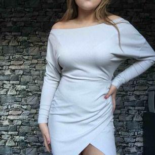 Ljusgrå klänning med din slits, ribbad i tyget.
