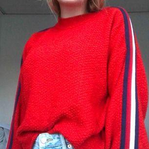 En röd stickad tröja med en blå och vit rand på varje arm. Vida armar. Den är i stl M men jag är däremot en S och den sitter jätte fint på mig. Köparen står för frakten som ligger på 60 kr☺️