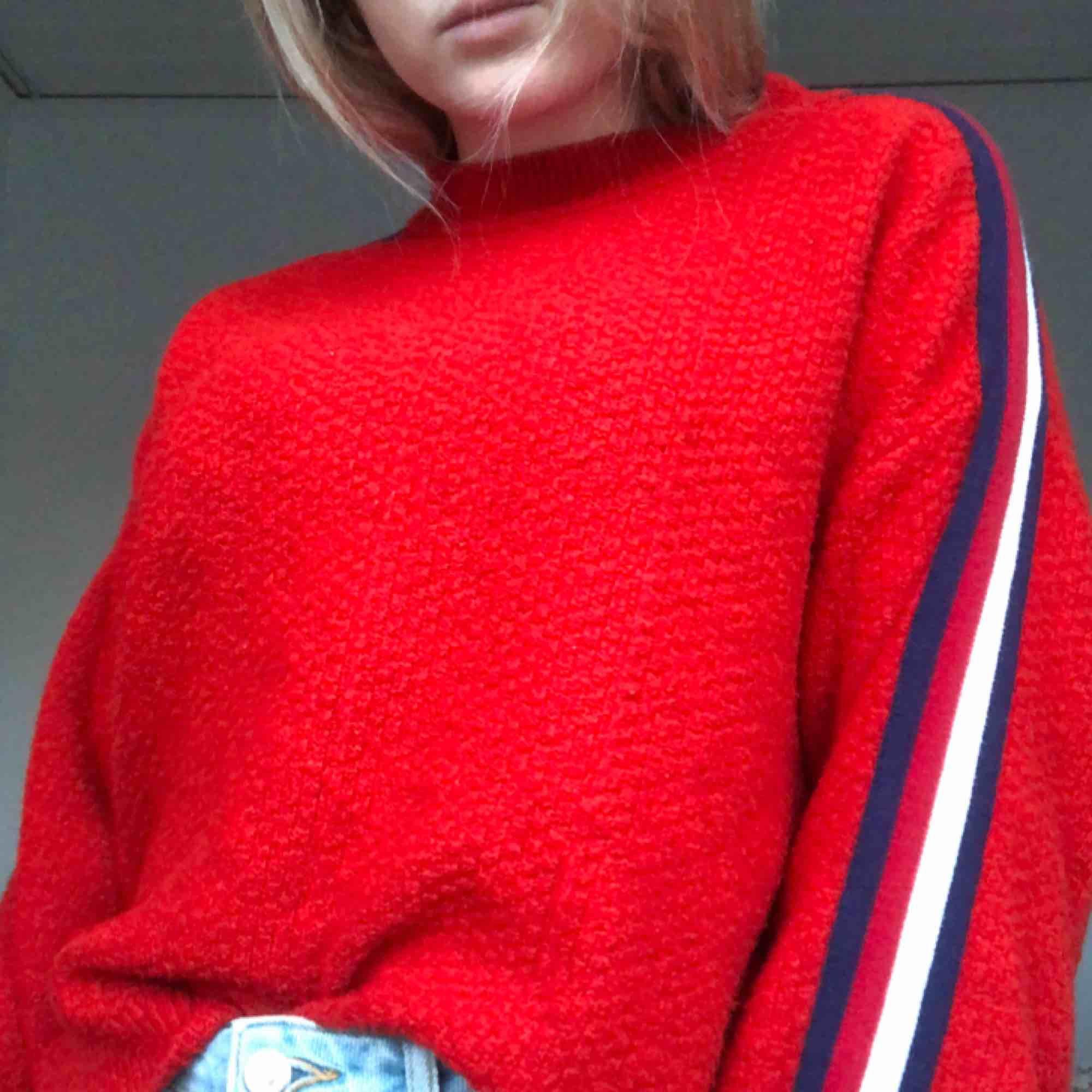 En röd stickad tröja med en blå och vit rand på varje arm. Vida armar. Den är i stl M men jag är däremot en S och den sitter jätte fint på mig. Köparen står för frakten som ligger på 60 kr☺️. Stickat.