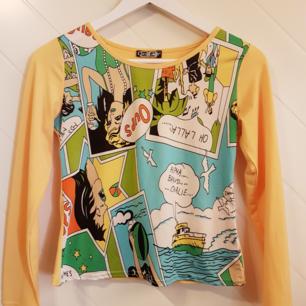 Jättefin, annorlunda tröja från Coco girls. Står ingen storlek men är gissningsvis strlk S. Tryck på framsida i serietidningsstuk med gula ärmar och rygg. Knappt använd.  Frakt tillkommer