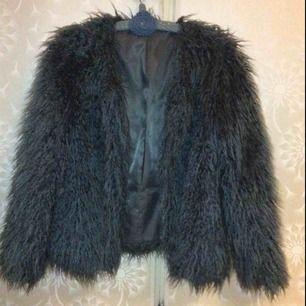 En blå fluffig jacka utan knappar eller dragkedja superskön på vintern.