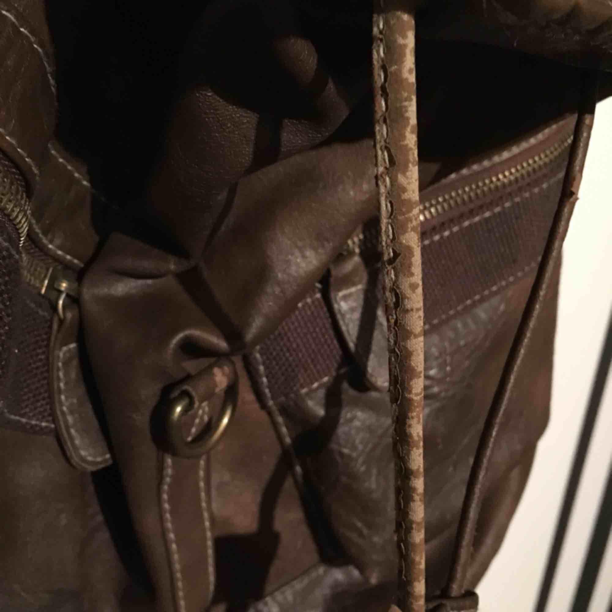 En brun fakeläder väska. Axelremmarnas fästningar är slitna , ett hål i innerfodringen och slitning på remmen (se bild 3).Men fortfarande fullt funktionsduglig.  Jag möts bara på plats, i Uppsala eller Täby. Betalning sker genom swish eller kontant.   . Väskor.