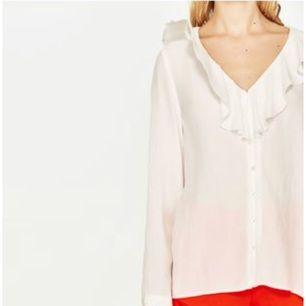 Vit blus med knäppning och volang urringning från Zara. Strl XS