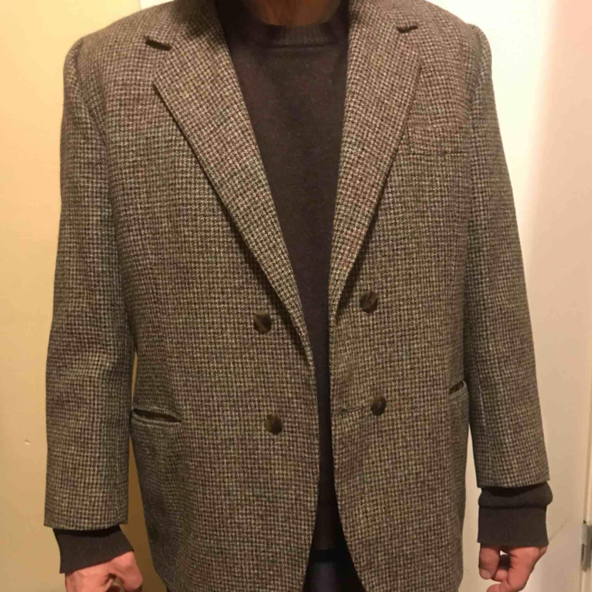 Harethorn Tweed 100% ull svartgrått, ljusgrått, mellangrått, grönt diskret rutigt Passar 160-170cm med större mage Över axlarna som stl.48-50 (jag väger 68kg) 108cm över magen Falskt dubbelknäppt, kan sprättas bort. Jackor.