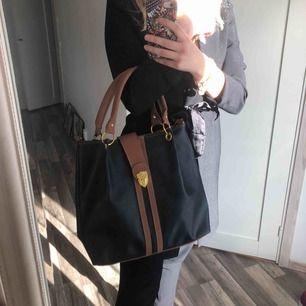 Jättesnygg väska i svart & brunt med gulddetaljer! Perfekt skick. Fack inuti & på baksidan. Fri frakt