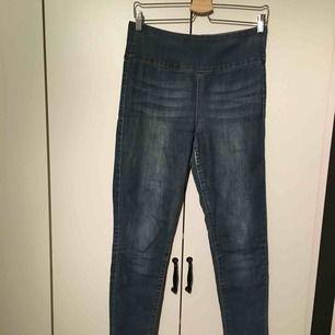 Ett par blåa högmidjade jeans med dragkedja baktill. En slitning på insida lår (se bild 3). Men annars i bra skick.   Jag postar tyvärr inte for tillfället, utan möts bara på plats, i Uppsala eller Täby. Betalning sker genom swish eller kontant.