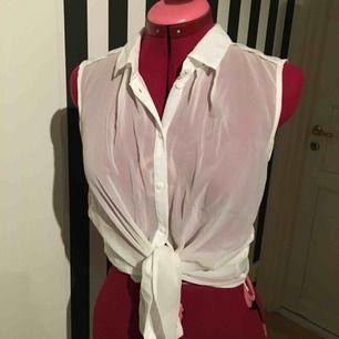 En kortärmad vit genomskinlig skjorta. Uppknuten på första bilden, men kan användas på båda sätt. I normalt begagnat skick.   Jag postar tyvärr inte för tillfället, utan möts bara på plats, i Uppsala eller Täby. Betalning sker genom swish eller kontanter.