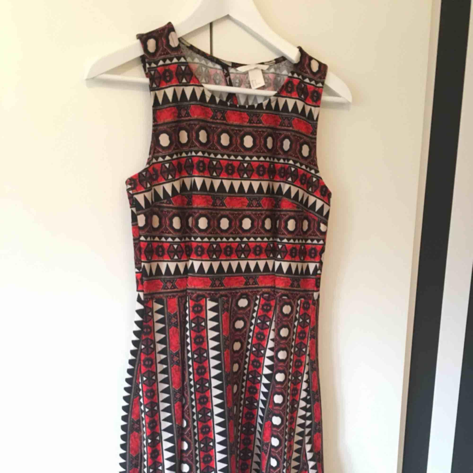 f87887f7ac0b En svart, vit och orange mönstrad klänning, i skater dress stil.