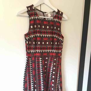 En svart, vit och orange mönstrad klänning, i skater dress stil. Den är dock insydd i midjan (se bild 3), men enkelt att sprätta om man vill. Jag kan posta eller mötas i Uppsala/Täby. Betalning sker genom swish eller kontanter.