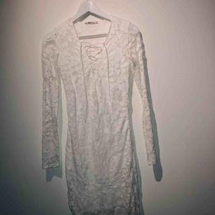 Spetsklänning med snörning vid brösten. Tajt passform som ger fin figur.