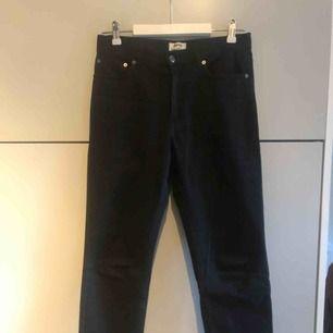 """Jeans från Acne Studios i perfekta boyfriend-fit-modellen """"Boy Black"""". Hög midja, raka ben, oversize passform. Normal/något stor storlek 26/32. Knappt använda men med avklippta ben. Slutar vid ankeln för dig som är runt 170."""