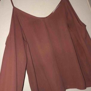 En blus från NA-KD som har ett hål vid ärmen på ena sidan.  Vädligt skön och snygg tröja att ha på fest.