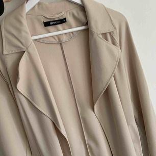 Beige kappa som aldrig är använd! Den har fickor och ett band som går att knyta runt, ha hängandes eller ta av helt.