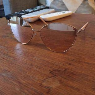 Helt oanvända solglasögon med rosa spegelglas. Fodral ingår i priset.