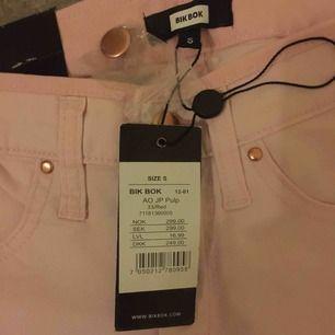 Helt nya ljusrosa jeans från BIKBOK. Storlek S. Med dragkedjor längst ner på benen. Med roséfärgade knappar. Extra knapp följes med i en liten påse. Normal vid midjan. Kan skickas.