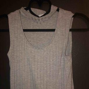 Ett grått linne med choker. Storlek XS, använd få gånger. Säljer pga använder inte längre och för liten. Frakt 9kr