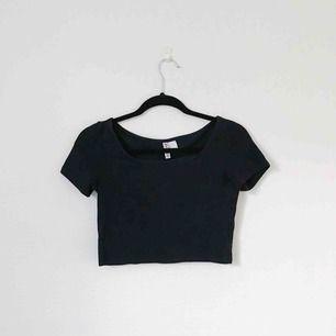 Svart croppad T-shirt från H&M Divided i storlek S. Bra basicplagg att matcha till högmidjade byxor! Frakt på 20 kronor tillkommer.