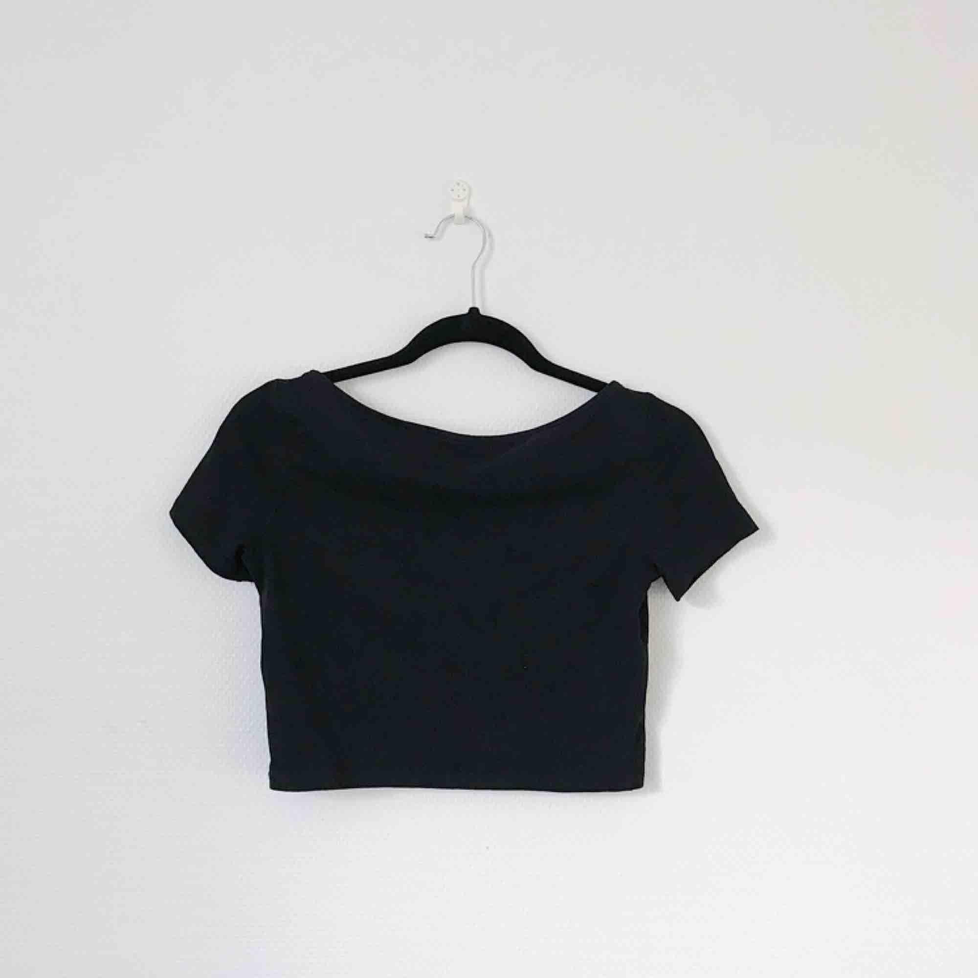 Svart croppad T-shirt från H&M Divided i storlek S. Bra basicplagg att matcha till högmidjade byxor! Frakt på 20 kronor tillkommer. . T-shirts.
