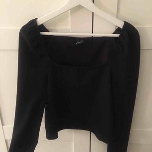 Svart långärmad tröja med puffiga axlar och rak låg skärning fram, skit snygg modell