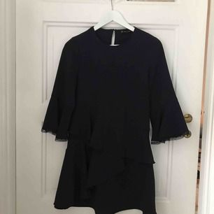Oanvänd mörkblå klänning med volanger, och spetsning på ärmar. Strl XS men passar även minde S
