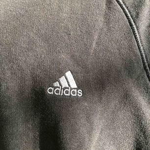 Svart Adidas tjocktröja med huva, väldigt snygg med jeans eller shorts en sommarkväll.