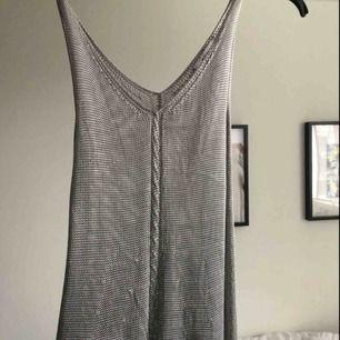 """Silvrig """"stickad"""" vintage klänning från asos, köpt i London under tidigt 90-tal. Faller på kroppen efter ens kurvor! I fint skick förutom ett litet uttänjt hål. Finns silvrig body att köpa till att ha under! ✨"""