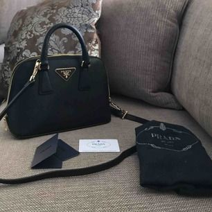 Supersnygg prada Axelremsväska i äkta läder, kan självklart bäras som en vanlig handväska om man önskar då extra bandet är avtagbart, aldrig använd helt ny. Inte äkta men kopia i hög kvalité   Dustbag och lappar medföljer