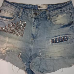 Slitna jeans med nitar.