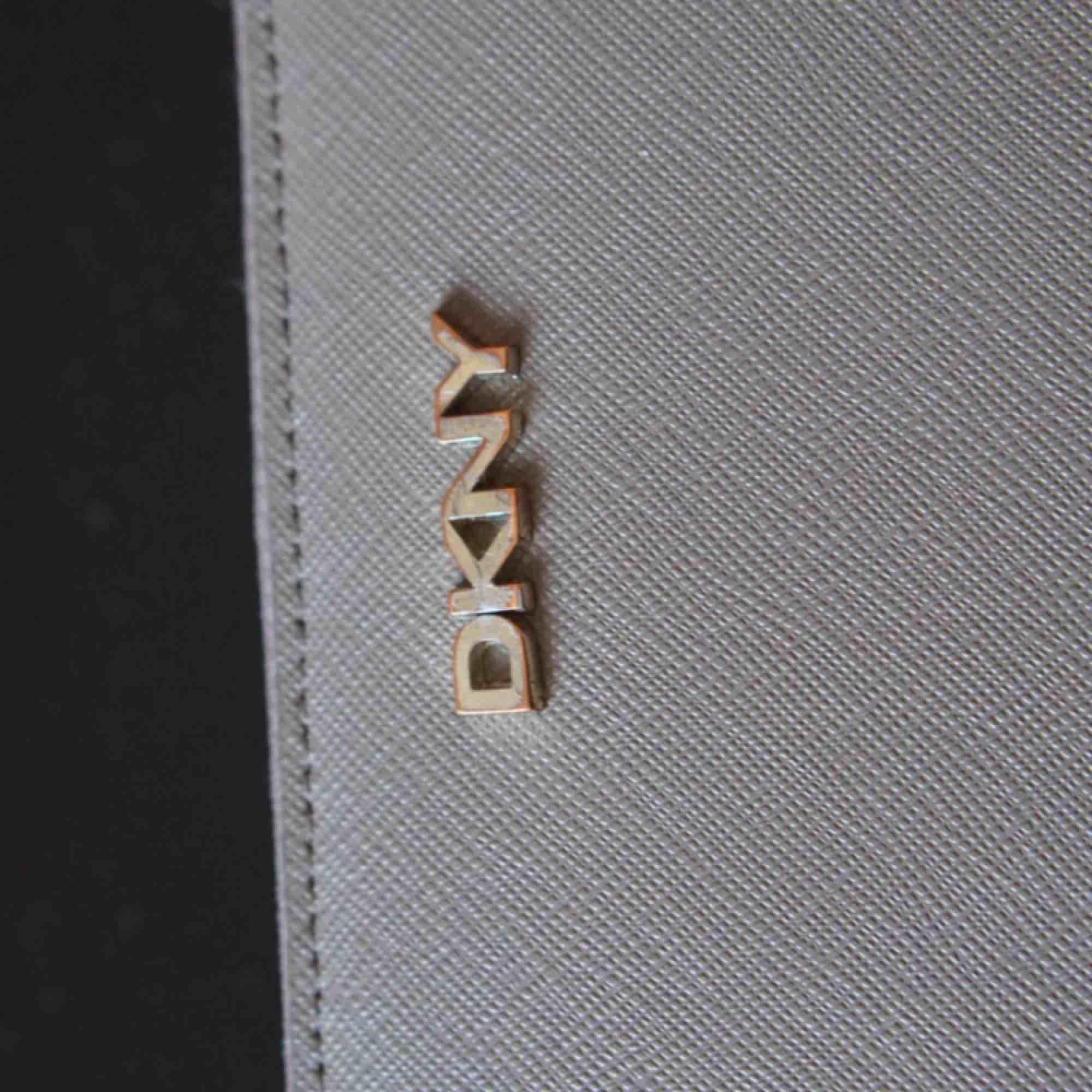Beige DKNY plånbok. Har ej kvar kvitto, men plånboken är äkta och inköpt i Dubai för antal år sedan. Guldet har börjat tappa sin färg, men är i  399 kr ex frakt eller mötas i Stockholm för 399 kr.  Varan finns på andra köp och sälj sidor 🌟. Accessoarer.