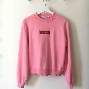 En rosa sweatshirt med NA-KD tryck i rött. Använd en gång, i princip nyskick.