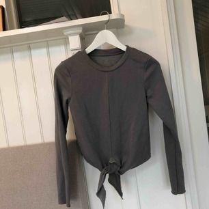 En grå, långärmad tröja från H&M med knyte som man justerar själv. Endast använd 2-3 gånger. Ser rosafläckig ut på bild pga ljuset ☺️ Köparen står för frakten