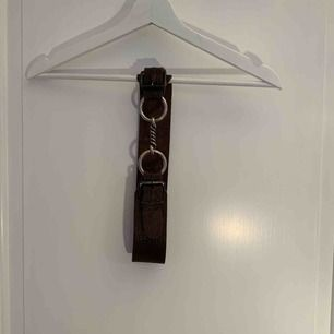 Vintageskärp i läder med metallspänne. Fint att använda för att markera midjan. Det går att justera omkretsen mellan ca 71-77 cm.