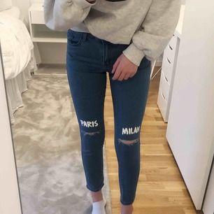 Mörkblåa jeans från forever 21 med texten Milan & Paris + slitningar över knäna Använda 2 gånger