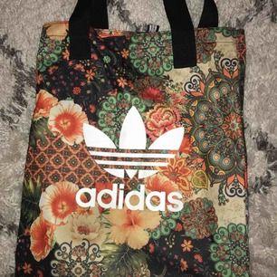 Adidas väska i ett coolt mönster. Lätta slitningar på loggan, med dom är knappt märkbara. Frakt ingår!