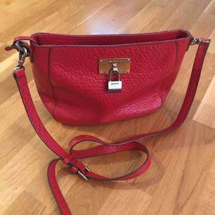 Röd DKNY axelremsväska. Slitningar på metallbrickan.(se bild)