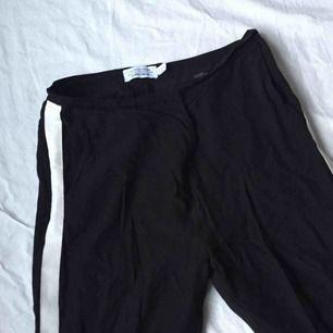 Svarta kostymbyxor med en vit rand längs benet från & Other Stories. Nypris 699kr. Köparen står för frakten! 🥳