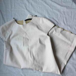 Älskad benvit skinnklänning från Zara. Lite trasig i ena armhålan (syns knappt), därav det låga priset. Nypris 699:- Köparen står för frakten.