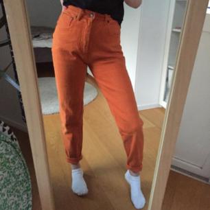 Ett par oranga byxor/jeans.