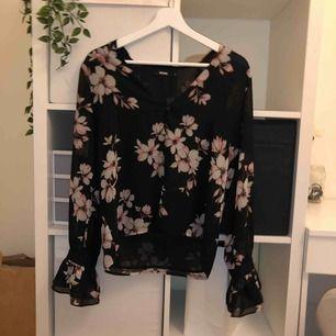 En svart blus med rosa blommor. Lite utsvängda ärmar vid handlederna