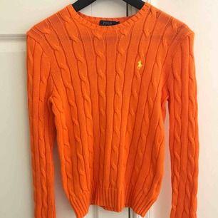 Klassisk, orange kabelstickad tröja från Ralph Lauren i bra skick. Använd ca 2 gånger. Jag möts upp i Stockholm eller köparen betalar frakten. Tar endast emot swish.