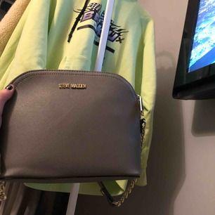 Väska från Steve Madden Ljusgrå med guldiga detaljer
