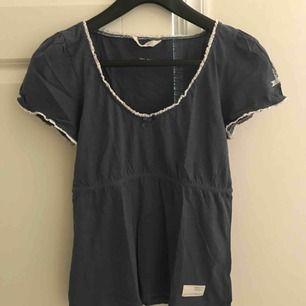 Klassisk t-shirt från Odd Molly i en grå/blå färg.  T-shirten är i bra skick. Jag möts upp i Stockholm eller så står köparen för frakten. Tar endast emot swish.