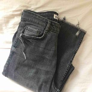 Stretchiga jeans med hög midja och slitningar på låren och vid vristerna. Använda ett fåtal gånger och i gott skick.