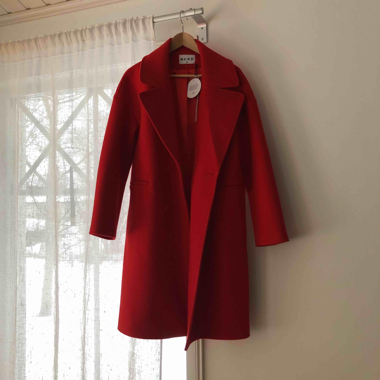 Röd dubbelknäppt kappa! Helt ny med lappen kvar. Aldrig använd så i perfekt skick! Nypris 1199kr. . Jackor.
