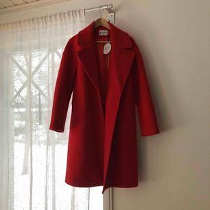 Röd dubbelknäppt kappa! Helt ny med lappen kvar. Aldrig använd så i perfekt skick! Nypris 1199kr.