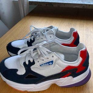 """Ett par Adidas i populära modellen """"Falcon"""". Använda några få gånger men ser ut som helt nya.  Färg: vit/blå med inslag av röd/lila"""